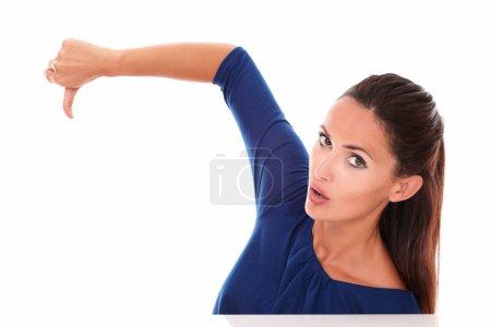 Photo pour Jolie fille en chemise bleue avec pouce baissé, geste mauvais travail, tout en vous regardant déçu par fond blanc - image libre de droit