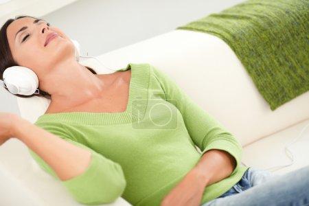 Photo pour Femme détendue reposant les yeux fermés tout en écoutant de la musique sur un casque avec la tête en arrière - image libre de droit