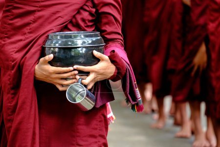 Detail of buddhist monks crowd and person holding a bowl and cup