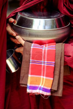 Close up of buddhist monk hands holding a bowl and cup