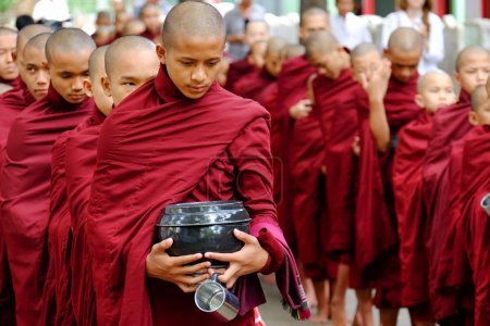 AMARAPURA, MYANMAR - JUNE 28, 2015: Buddhist monks queue for lun