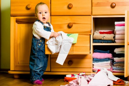 Photo for Baby throws out clothes from wooden furniture at home - Royalty Free Image