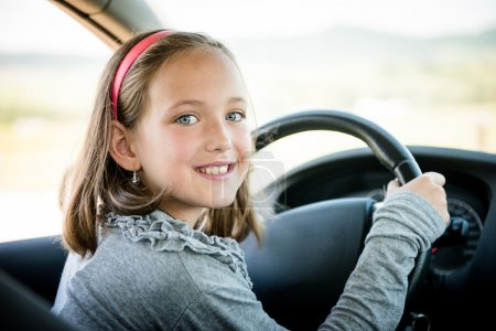 Photo for Child pretends driving car sitting on front driver seat with hands on steering - Royalty Free Image