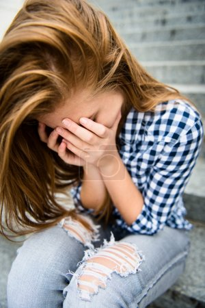 Photo for Unhappy depressed teenager with face in hands sitting outdoor - Royalty Free Image