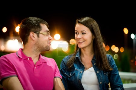 Photo for Couple together on date in street with neon lights at night - Royalty Free Image