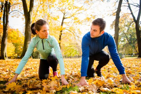Photo for Young couple in ready position prepared for running in autumn nature - Royalty Free Image