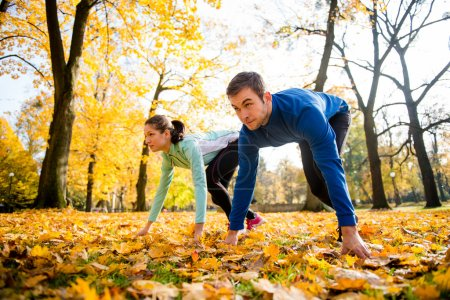 Photo for Young couple in steady position prepared for running in autumn nature - Royalty Free Image