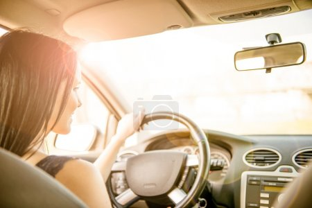 Photo for Young beautiful black-haired woman driving car - rear view - Royalty Free Image