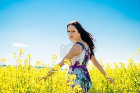 Photo pour Jeune belle femme jouissant de la vie dans le champ de colza florissant - image libre de droit