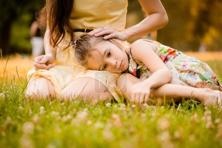 Photo for Mother is caressing her worried child outdoor in nature - Royalty Free Image