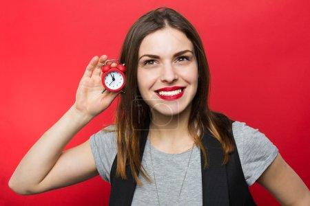 Photo pour Belle femme retenant l'horloge rouge - image libre de droit