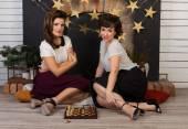 Dvě krásná dívka přátelé hraje šachy s krbem