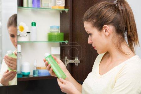 Photo pour Belle fille en choisissant des produits de beauté dans l'armoire de toilette - image libre de droit