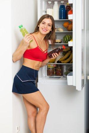 Sporty woman by the fridge
