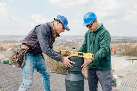 Photo pour Deux maîtres professionnels travailleurs de la construction Roofer réparation cheminée sur bardeaux d'ardoise gris toit de la maison domestique, fond ciel avec espace de copie. - image libre de droit