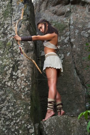 Primitive woman standing on a rock and holding a bow. Amazon woman