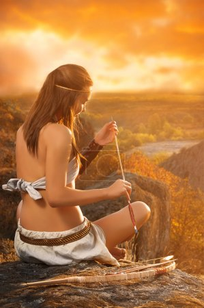 Primitive woman  holding a bow and arrow. Amazon woman