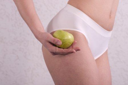 Slim woman holding an apple