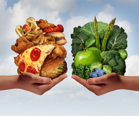 Photo for Nutrition choice and diet decision concept and eating choices dilemma between healthy good fresh fruit and vegetables or greasy cholesterol rich fast food with two hands holding food trying to decide what to eat. - Royalty Free Image