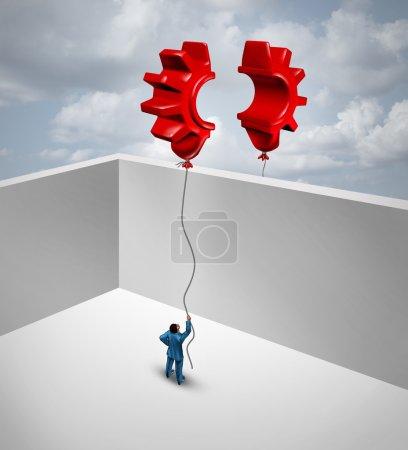 Foto de Superar las barreras comerciales como dos socios separados por muros en un esfuerzo conjunto para fusionar dos globos rojos voladores con forma de medio engranaje o engranaje como símbolo para el éxito comercial y soluciones comerciales globales. - Imagen libre de derechos