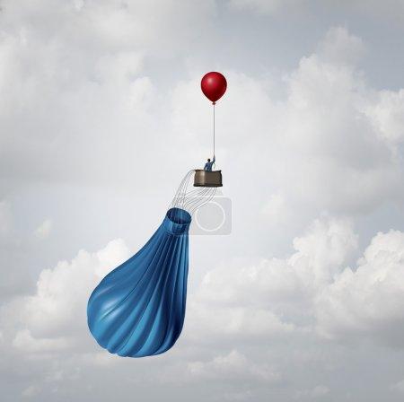 Photo pour Métaphore du affaires d'urgence plan et gestion de crise de la stratégie comme un homme d'affaires dans une montgolfière cassé des dégonflé, sauvegardée par un ballon unique petit parti rouge comme une idée de solution de réponse innovante. - image libre de droit