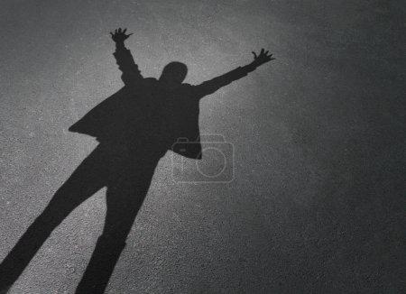 Photo pour Le succès de l'entreprise en tant qu'ombre d'un homme d'affaires prospère célébrant les bras en l'air sur un fond de chaussée en tant qu'entrepreneur gagnant . - image libre de droit