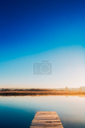 Photo for Old Wooden Boards Pier On Calm Water Of Lake, River. Autumn Season. Sunset, Sunrise Time - Royalty Free Image