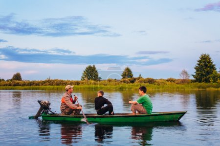 Belarusian Man And Two Boys Sailing In Old Boat On River At Suns