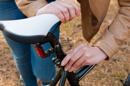 Photo for A young woman repairs a bicycle in the bicycle expedition - Royalty Free Image