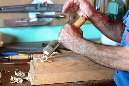 Cabinetmaker carving a piece of wood with chisel and using his h