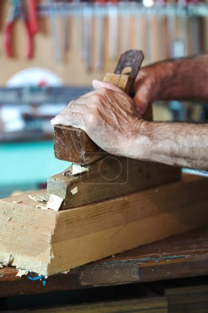 Hands of a cabinetmaker sanding