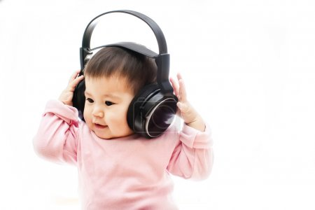 One  small happy baby girl listens radio music song with headphone with hands