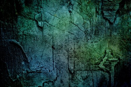 Ancient dark blue-green texture concrete wall. Grunge surface is covered with cracks and scratches. A bright spot in the center surrounded by shadow.