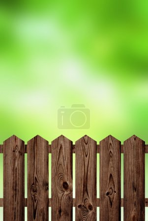 Dark wooden fence on a bright green blur background. Summer or spring landscape shows soft fresh herbs garden, forest, suburban or rural areas. Pleasant chores in your garden.
