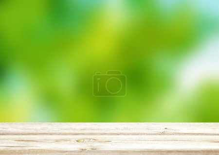 Light wooden surface of a table or bench in a spring garden. Light summer blur green background.