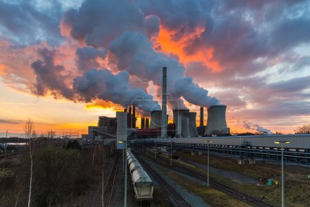 Coal-fired power plant with burning sunset sky