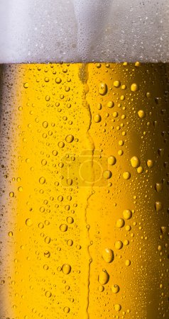 overflowing beer in a glass with dew drops