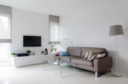 Photo pour Salon blanc avec canapé en cuir taupe et table en verre - image libre de droit