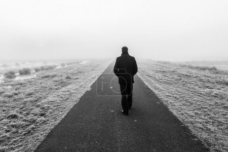 Man walking on an empty desolate raod