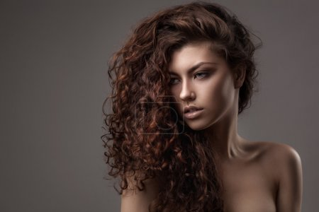 Photo for Studio shot of woman with healthy brown curly hair isolated over grey background - Royalty Free Image
