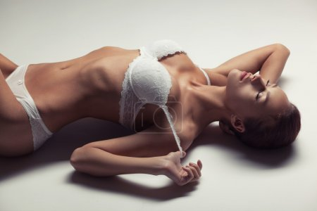 Photo for Beautiful young girl in white lingerie lying on a light background - Royalty Free Image