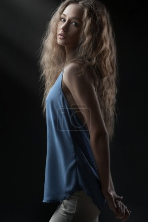 Photo for Studio portrait of young woman with curly hair on dark background - Royalty Free Image