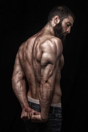 Photo for Strong athletic beardy mans back isolated over black background - Royalty Free Image