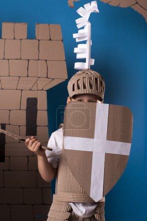 Photo pour Photo du garçon en costume chevalier médiéval fait de cartons. Cette décorations sont faites spécialement pour cette photosession par moi. - image libre de droit