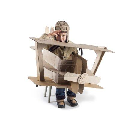 Photo pour Garçon dans un costume de pilotes rend hommage. L'action se déroule près de l'avion en carton. - image libre de droit