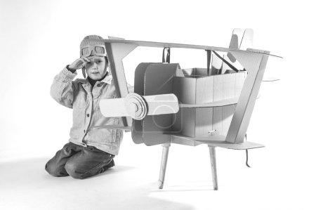Photo pour Le garçon dans un costume de pilotes salue. L'action se déroule près de l'avion en carton. Photo en noir et blanc. - image libre de droit