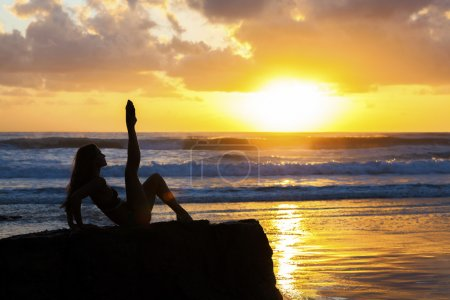 Fit woman stretching on beach at sunrise