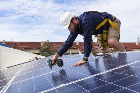 Photo pour Technicien de panneaux solaires avec perceuse installant des panneaux solaires sur le toit - image libre de droit