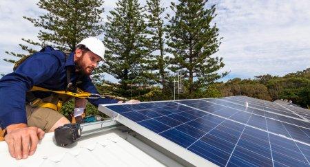 Foto de Técnico de panel solar con taladro instalar paneles solares en el techo - Imagen libre de derechos