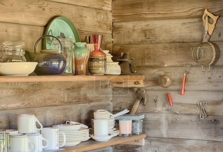 Photo pour Une image de la nature morte des étagères de cuisines dans une vieille cabane en rondins montrant les assiettes, les tasses, les bols et autres articles de ménage disposés sur chaque étagère . - image libre de droit
